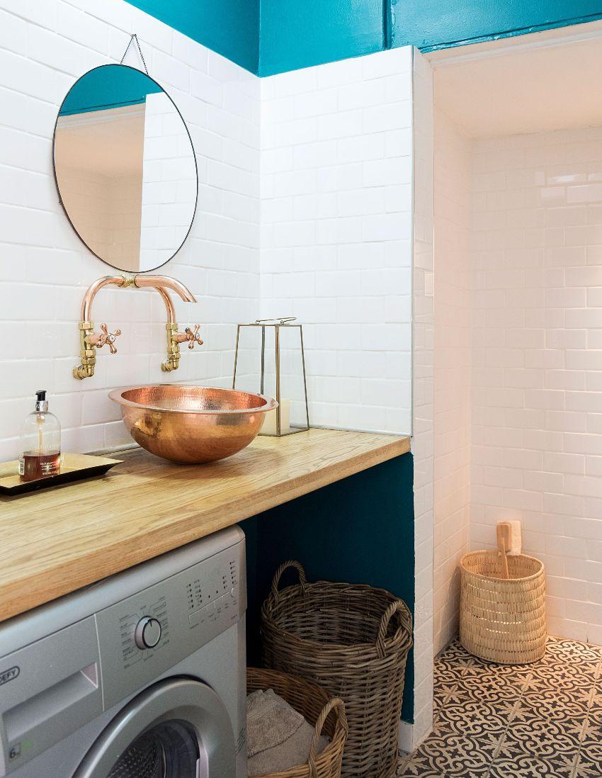 Разместив раковину и машинку под одной столешницей, можно сэкономить пространство небольшой ванной